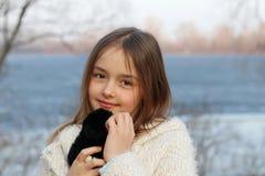 Härlig liten brunögd flicka som ser kameran som kramar hennes mjuka leksak arkivbild