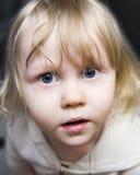 Härlig liten flicka blondinen med enorma blåa ögon som ser upp Arkivfoto