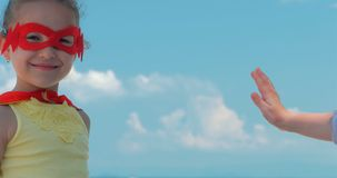Härlig liten flicka för nära övre stående i superherodräkten som är iklädd en röd kappa och maskeringen av hjälten give arkivfilmer