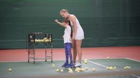 Härlig liten flicka för undervisning för kvinnatennislagledare hur man spelar tennis stock video