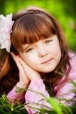 Härlig liten flicka i den blommiga trädgården Arkivfoto