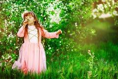 Härlig liten flicka i den blommiga trädgården Arkivbilder