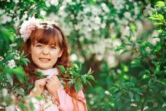 Härlig liten flicka i den blommiga trädgården Arkivfoton
