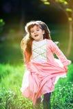 Härlig liten flicka i den blommiga trädgården Arkivbild