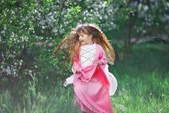 Härlig liten flicka i den blommiga trädgården Royaltyfri Bild