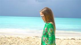 Härlig liten flicka i klänning på stranden som har gyckel arkivfilmer