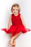 Härlig liten flicka i röda klänningar royaltyfria bilder