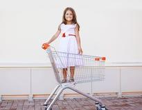 Härlig liten flicka i shoppingvagnen som har roligt utomhus Royaltyfri Foto