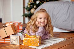 Härlig liten flicka med blont hår med lockigt hår som ligger på golvet nära sängen i bakgrundsjulgranen royaltyfri bild