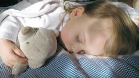 Härlig liten flicka med blont hår som sover på sängen och tänder av solen som är uppochnervänd med en nallebjörn arkivfilmer