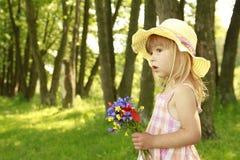 Härlig liten flicka med en bukett av blommor i natur Royaltyfri Fotografi