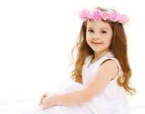 härlig liten flicka med en krans av blommor på honom Royaltyfria Bilder