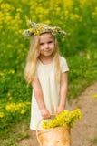 Härlig liten flicka med en krans på hennes huvud som spelar i en flo fotografering för bildbyråer