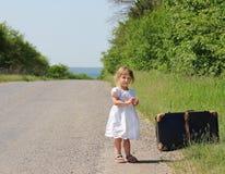 Härlig liten flicka med en resväska Arkivfoton
