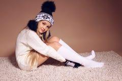 Härlig liten flicka med långt blont hår i slags tvåsittssoffa stucken kläder Arkivfoton