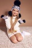 Härlig liten flicka med långt blont hår i slags tvåsittssoffa stucken kläder Royaltyfri Bild