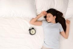 Härlig liten flicka med ringklockan som sover i säng, bästa sikt royaltyfri fotografi