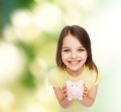 Härlig liten flicka med spargrisen Arkivbilder