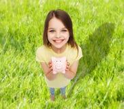 Härlig liten flicka med spargrisen Fotografering för Bildbyråer