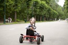 Härlig liten flicka med två svansar som ler i den mer snälla bilnollan Arkivbild