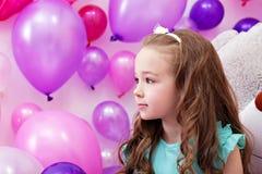 Härlig liten flicka på bakgrund av ballonger arkivfoton