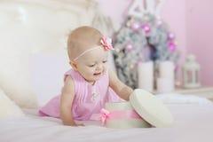 Härlig liten flicka som öppnar en julgåva, bakgrundsträdet Royaltyfri Foto