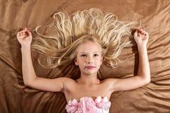 Härlig liten flicka som drömmer på säng Fotografering för Bildbyråer