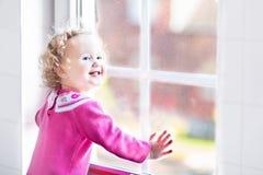 Härlig liten flicka som håller ögonen på ut ur ett fönster Fotografering för Bildbyråer