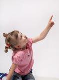 Härlig liten flicka som indikerar på något fotografering för bildbyråer