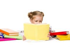 Härlig liten flicka som läser boken royaltyfria bilder