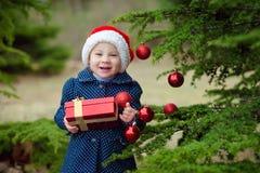 Härlig liten flicka som ler i ask för gåva för santa hattinnehav nära julgranen royaltyfri fotografi