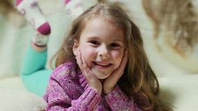 Härlig liten flicka som ler på kameran Stående av den gladlynta ungen som ligger på soffan stock video