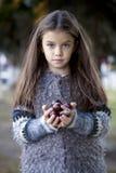 Härlig liten flicka som rymmer en kastanj arkivfoto