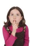 Härlig liten flicka som ser upp, och göra en gest tystnad Royaltyfri Bild