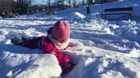 Härlig liten flicka som spelar i snö Ungen har gyckel på snö Tyck om ferie arkivfilmer