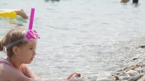 Härlig liten flicka som spelar på havet, gulligt le i en maskering och respiratorröret för att simma 4K stock video