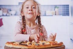 Härlig liten flicka som tycker om en läcker pizza i naturmat arkivfoto
