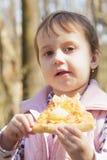Härlig liten flicka som utomhus tycker om en läcker mat för pizza, royaltyfria bilder