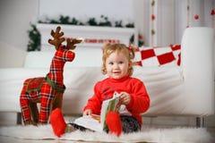 Härlig liten flicka som väntar på ett mirakel i juldecorat Arkivbild