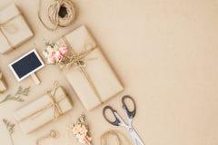 Härlig liten handgjord packe för DIY-gåvaask med blommor och dekorativt rep på brun bakgrund retro stiltappning plant arkivbilder