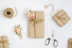 Härlig liten handgjord packe för DIY-gåvaask med blommor och dekorativt rep på vit bakgrund retro stiltappning plant arkivbilder