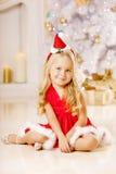 Härlig liten jultomtenflicka nära julgranen lycklig flicka royaltyfri bild