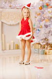 Härlig liten jultomtenflicka nära julgranen Lycklig gir Arkivbild