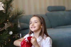 Härlig liten le flicka som tar julgåvor ut ur röd traditionell påse med hopp i henne ögon arkivbild