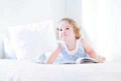 Härlig liten litet barnflicka med läseboken för lockigt hår Royaltyfri Foto