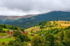 Härlig liten by som omges av berg och skogar royaltyfria bilder
