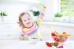 Härlig litet barnflicka med lockigt hår som har frukosten Royaltyfri Foto