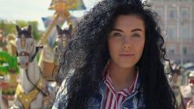 Härlig lockig brunett på bakgrunden av karusellen stock video