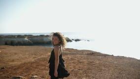 Härlig lockig flicka som poserar på kamera nära havet arkivfilmer