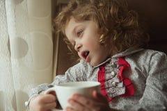 Härlig lockig-haired liten flicka med en kopp Arkivfoto